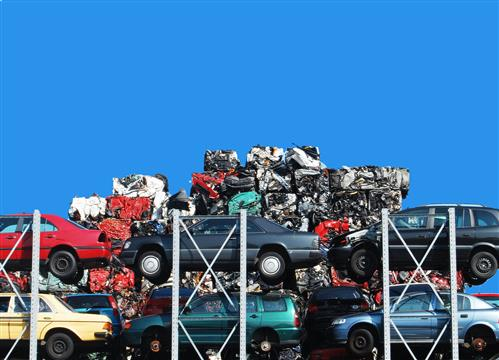 There is a stack of cars in a junkyard